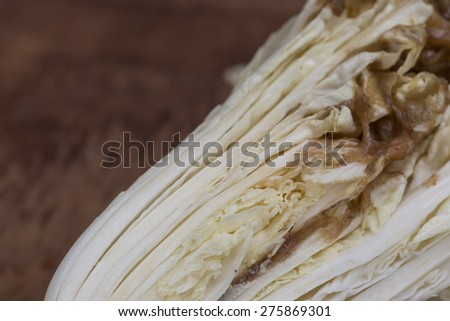 Cabbage leaves decomposing  on wood - stock photo