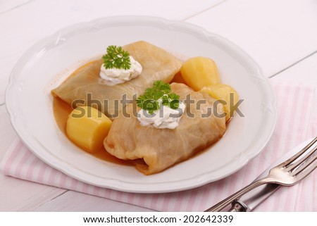 Cabbage rolls with potato and sour cream, close up - stock photo