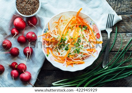 Cabbage salad.  cabbage salad with sweet carrot, radish, bow in a white bowl. Coleslaw salad in white bowl on a brown background. fresh vegetables salad with cabbage and carrot. Rustic style - stock photo