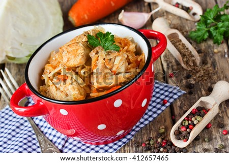 Cabbage stew with meat on red bowl with dots, hearty rustic dish selective focus - stock photo