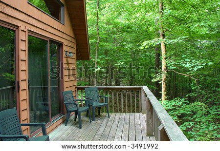 Cabin and wooden deck in the woods - stock photo