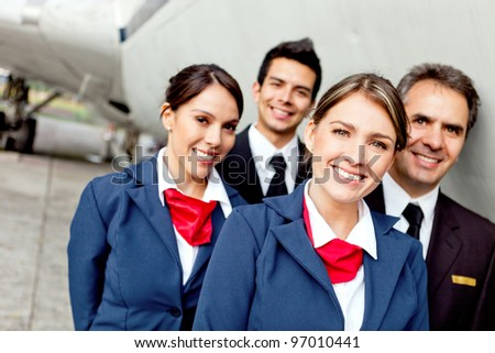 Cabin crew team with pilots and flight attendants smiling - stock photo