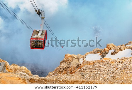 Cabin of ropeway in mountains among clouds in the sky. - stock photo