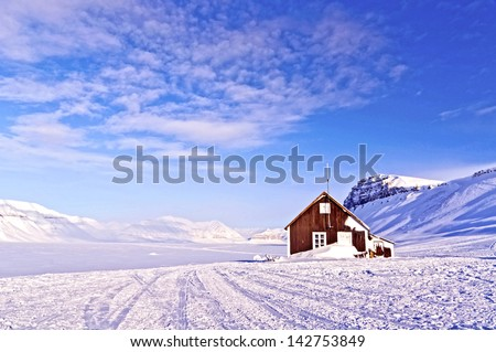 Cabin of wood in the middle of a paradise frozen in the Arctic Norwegian - stock photo