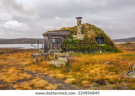 Cabin with turf roof near Hardangervidda National Park with a lake in the background, Hordaland county, Norway - stock photo