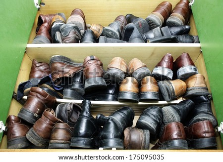Cabinet full of old leather shoes - stock photo