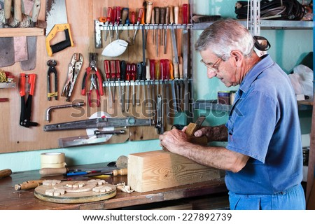 cabinetmaker sanding a piece of wood in his workshop with tools on the background / carpenter working with wood  - stock photo