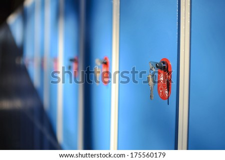 Cabinets with locks, a few keys inserted with a red element. - stock photo