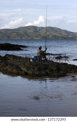 CABLE BAY,NZ-APR 22:Mature Maori man fishing from the beach on April 22 2013.New Zealand exclusive economic zone covers 4.1 million square kilometers and It's the sixth largest zone in the world.