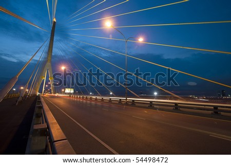 Cable bridge at evening with highway road - stock photo