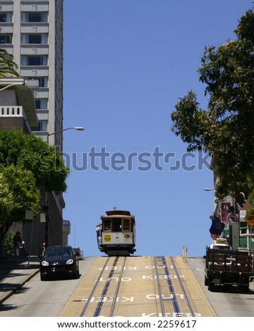 Cable car crests a hill in San Francisco California silhouetted against a deep blue sky - stock photo