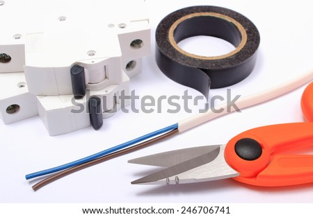 Cable cutter, electric wire and fuse, insulating tape lying on white background, accessories for engineer jobs, repair of cable - stock photo