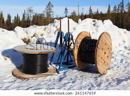Cable drums prepared for installation in northern snowy forest - stock photo