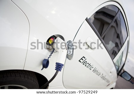 Cable hanging down from gas tank location on electrical vehicle. Outdoors - stock photo