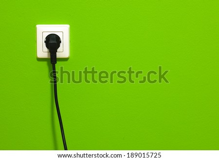 Cable in connector plug on green wall - stock photo