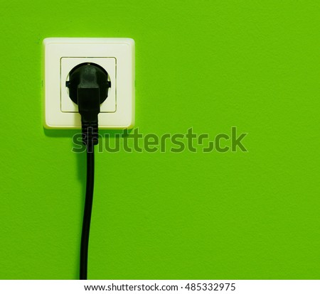 Cable in connector plug on green wall
