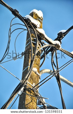 Cable lines on a pole against a blue sky - stock photo