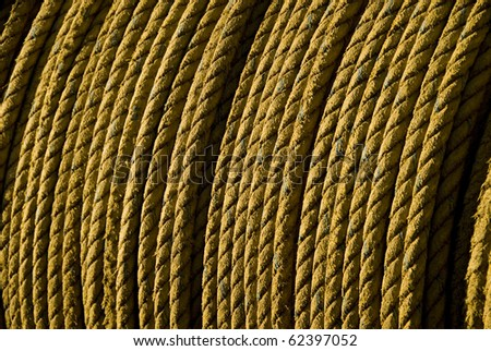 Cable of yellow rope on fishing boat - stock photo