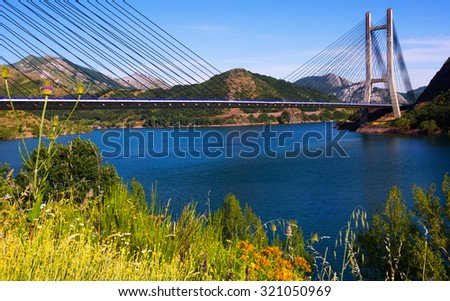 Cable-stayed bridge over lake in mountains of  Leon - stock photo