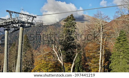 Cable way in the Caucasian mountains, autumn nature, peaks in the haze of clouds