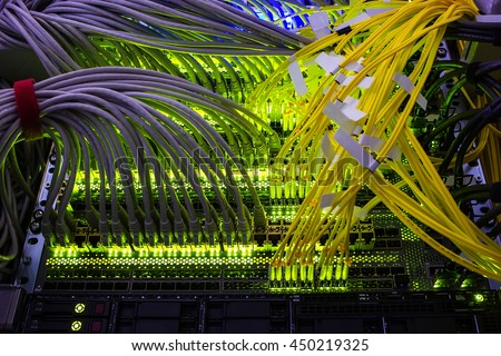 cables connected to an optic ports and UTP Network cables connected to ethernet ports. - stock photo
