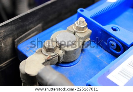 Cables connected to car battery under hood of car - stock photo