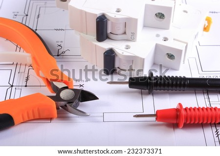 Cables of multimeter, metal pliers and electric fuse on construction drawings, electrical drawings and tools for engineer jobs