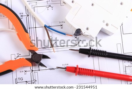 Cables of multimeter, metal pliers, electric wire and fuse on construction drawings, electrical drawings and tools for engineer jobs - stock photo