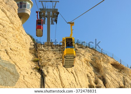 Cableway with two, yellow and red, cabins in Rosh Hanikra Israel - stock photo