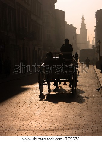Cabman driving the tourists in a carriage in the morning - stock photo
