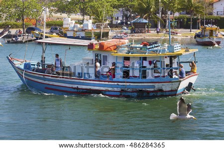 Cabo Frio, Brazil september 17th, 2016 A fisherboat arrives a fishermen village followed by an albatross
