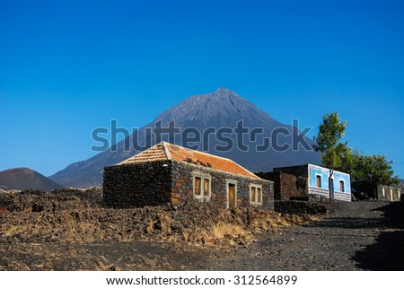 Cabo Verde, Pico do Fogo, Caldera. Volcano Pico do Fogo, 2829 m, the highest mountain of Cabo Verde standing isolated in the burned Lava fields. Hauses of igneous rocks in the Cha das Caldeiras. - stock photo