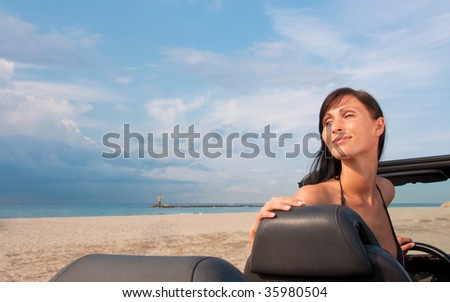 Cabriolet woman parking on the beach with ocean sea and coastline in background - stock photo