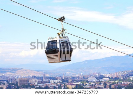 Cabs cable car against the sky and city