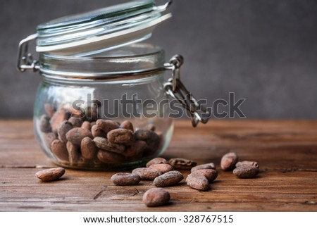 Cacao beans in a glass container - stock photo