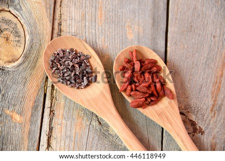 Cacao nibs and acai berries on spoons on wood - stock photo