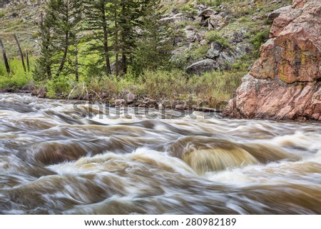 Cache la Poudre River west of  Fort Collins in northern Colorado - springtime scenery with a snow melt run off - stock photo