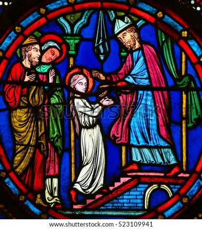 CAEN, FRANCE - FEBRUARY 12, 2013: Stained Glass window in the Cathedral of Caen, Normandy, France, depicting the Blessed Virgin Mary with her parents Saint Joachim and Anna, as a young girl