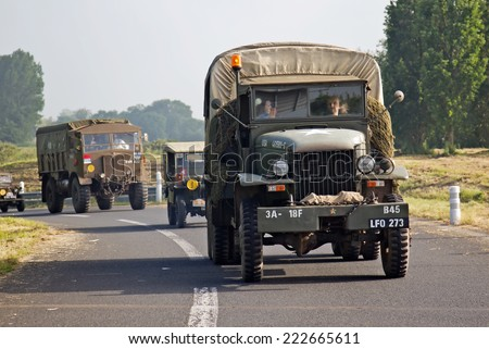 CAEN, FRANCE - MAY 30: A convoy of WW2 British army vehicles led by a Jimmy GS truck makes there way to the D-Day 70th anniversary celebrations at Port-en-Bessan on May 30, 2014 in Caen - stock photo
