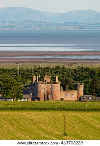 Caerlaverock Castle shown within the landscape giving its position next to the Solway Firth in Dumfries and Galloway near the Scottish Border with the English Lake District in the distance.