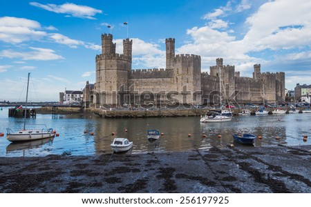 CAERNARFON, WALES - 29 SEPT. 2013: View on Caernarfon Castle from accross the river Seiont with anchored boats. The castle is a major landmark in Wales and attracts thousands of tourists each year - stock photo