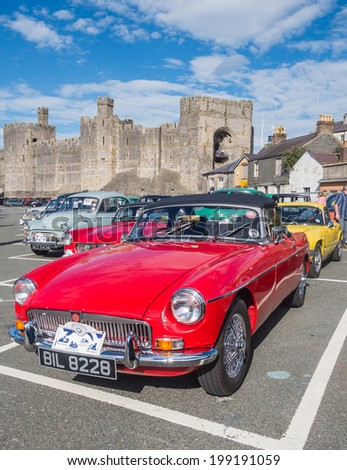 CAERNARFON, WALES - 29 SEPTEMBER 2013: Vintage classic cars taking part in the Walled Towns Trail Car Run 2013 are parked in front on Caernarfon Castle - stock photo