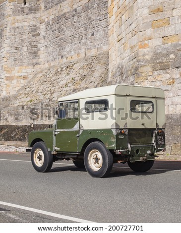 CAERNARFON, WALES - 29 SEPTEMBER 2013: Vintage classic LandRover car taking part in the Walled Towns Trail Car Run 2013 passes the walls of Caernarfon Castle en route to its next destination - stock photo
