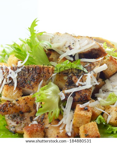 Caesar chicken salad with grated parmesan on white background - stock photo