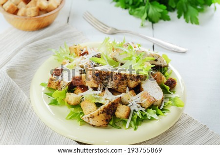 Caesar chicken salad with grated parmesan on white table - stock photo