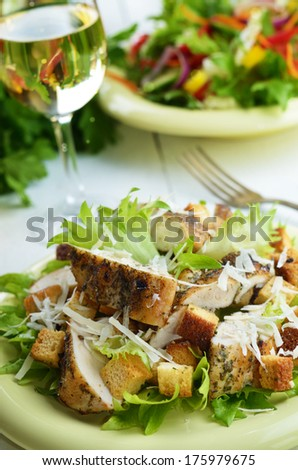 Caesar chicken salad with grated parmesan served with white wine - stock photo
