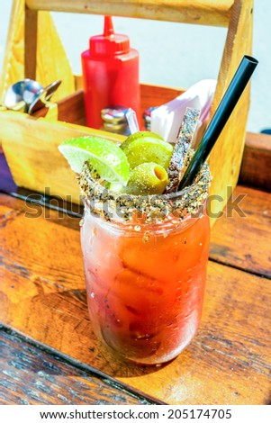 Caesar or bloody mary cocktail drink rimmed with spice and garnished with lime wedge, pepper, and olives on a hot summer day. - stock photo