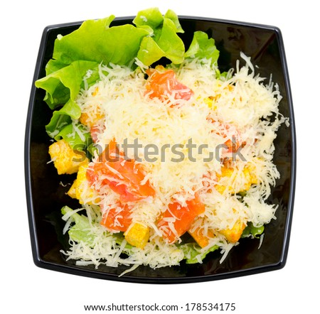 caesar salad in black bowl, isolated, top view - stock photo