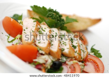 Caesar salad made of grilled chicken fillet garnished with parmesan cheese and fresh vegetables