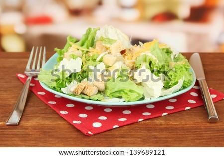 Caesar salad on blue plate, on bright background - stock photo